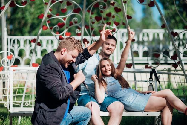 Szczęśliwi ludzie relaksuje na ławce śpiewa piosenkę i gestykuluje zwycięstwo