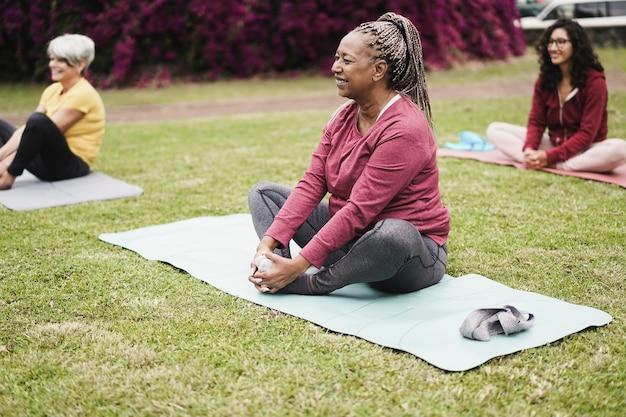 Szczęśliwi ludzie robią zajęcia jogi, utrzymując dystans społeczny w parku miejskim