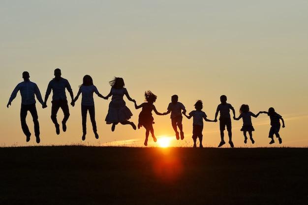 Szczęśliwi ludzie sylwetek outdoors na polu