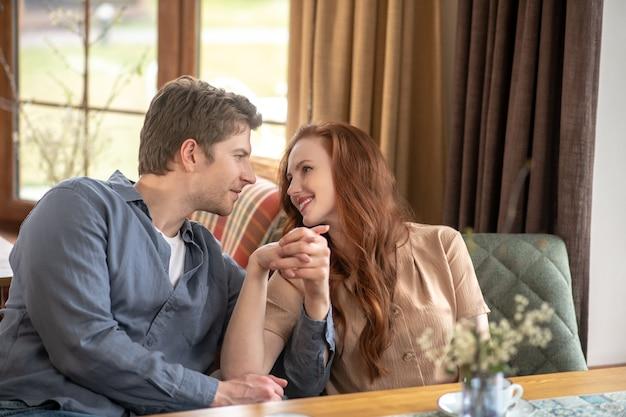 Szczęśliwi ludzie. szczęśliwa młoda dorosła kobieta z długimi rudymi włosami i uważny mężczyzna trzymający rękę siedząc w restauracji w ciągu dnia