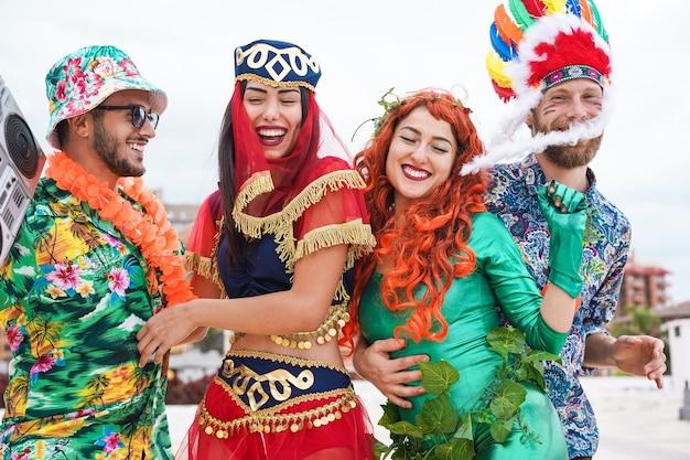 Szczęśliwi ludzie ubrani świętujący karnawał tańczą razem