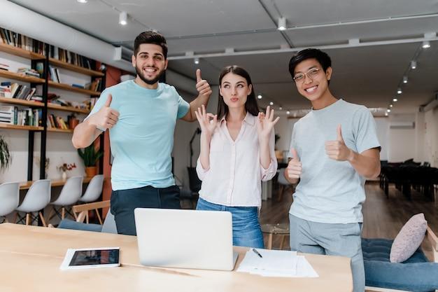 Szczęśliwi ludzie w wieku milenijnym pokazują kciuki w biurze
