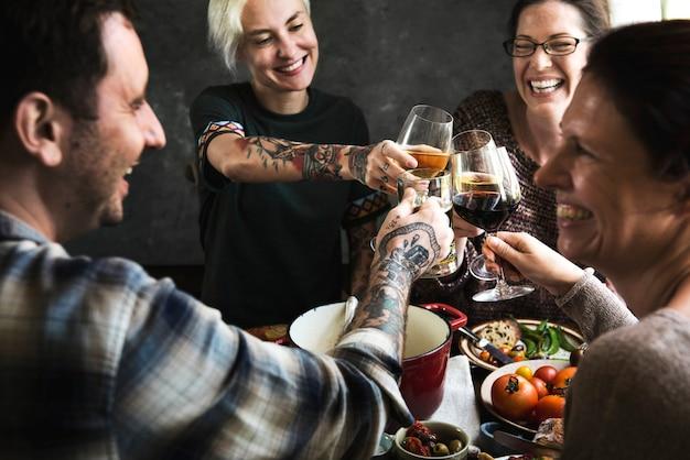 Szczęśliwi ludzie wiwatujący przy kieliszkach wina