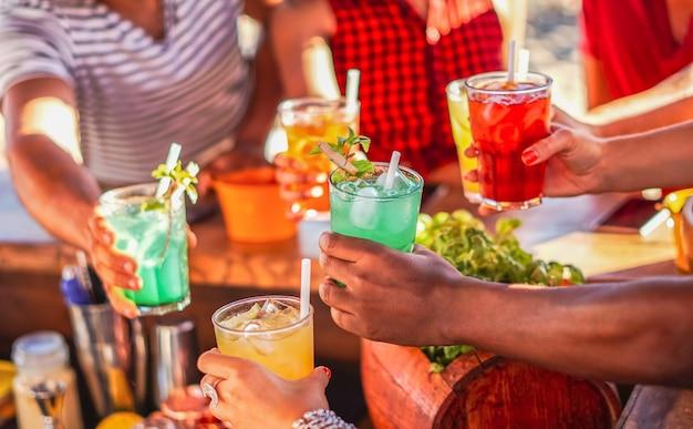Szczęśliwi ludzie wiwatujący z mojito i dobrze się bawiący - wielorasowi przyjaciele piją koktajle w barze na plaży w letnie dni z maską na twarz, aby chronić się przed koronawirusem