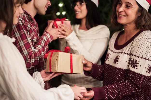 Szczęśliwi ludzie wymienia prezenty przy bożenarodzeniowym świętowaniem
