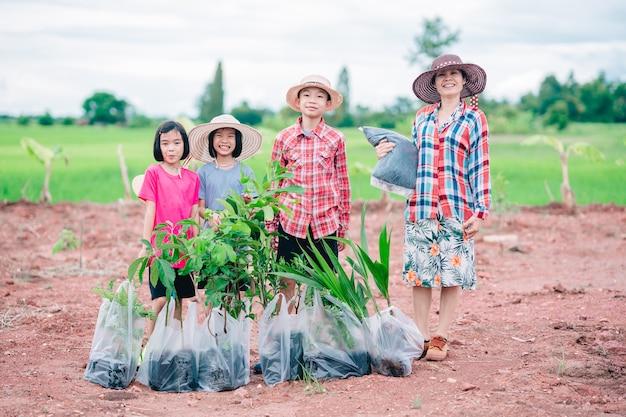 Szczęśliwi ludzie z rodziny trzymający sadzenie drzew do sadzenia w ogrodzie na ekologicznym zielonym polu ryżowym