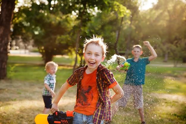 Szczęśliwi mali chłopiec bawić się z pistoletami na wodę