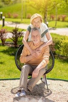 Szczęśliwi małżonkowie w średnim wieku pozują do kamery w ogrodzie