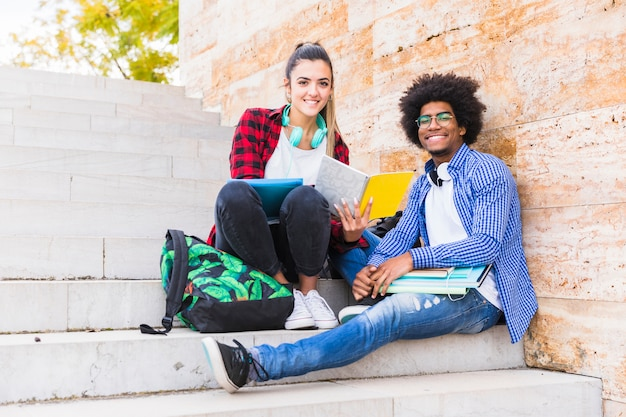 Szczęśliwi męscy i żeńscy studenci uniwersytetu siedzi na schody patrzeje kamera
