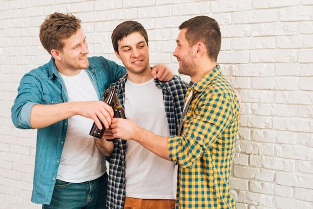 Szczęśliwi męscy przyjaciele stoi przeciw białej ścianie wznosi toast piwo butelki