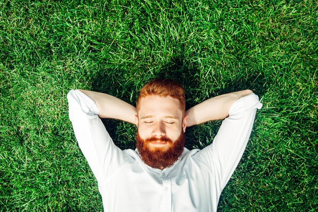 Szczęśliwi mężczyzna kłama na trawie. piękny model z czerwoną brodą w letni dzień.