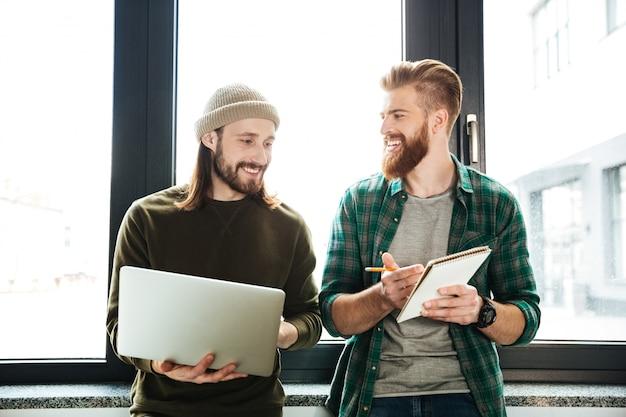 Szczęśliwi mężczyzna koledzy w biurze używać laptop
