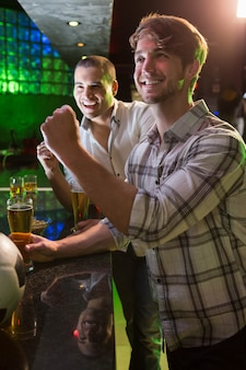 Szczęśliwi mężczyzna ogląda futbolowego dopasowanie w barze