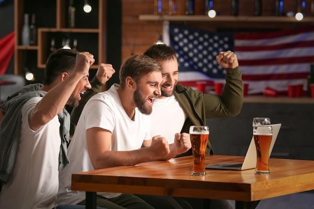 Szczęśliwi mężczyźni po wygraniu zakładów sportowych w pubie