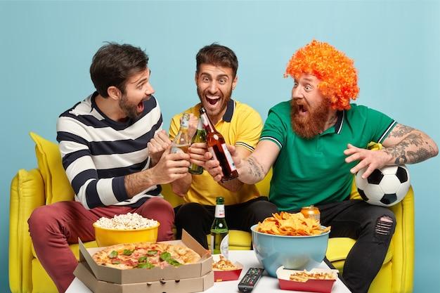 Szczęśliwi mężczyźni świętują zwycięstwo drużyny piłkarskiej, którą kibicowali, brzęczą butelkami piwa, oglądają turniej sportowy w domu, jedzą przekąskę, krzyczą zwycięsko. zadowoleni fani cieszą się ogólnopolską rywalizacją w telewizji