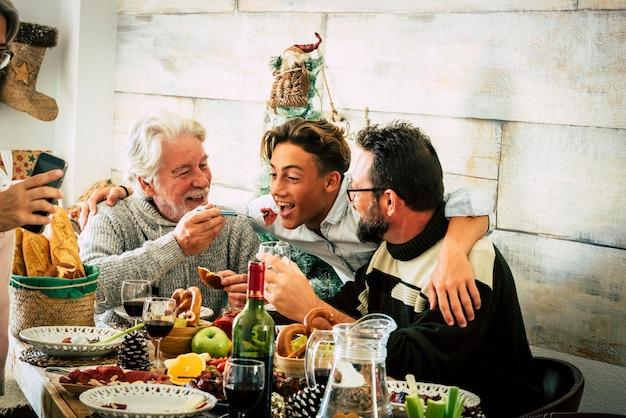 Szczęśliwi mężczyźni z rodziny wspólnie jedzą świąteczny obiad w domu