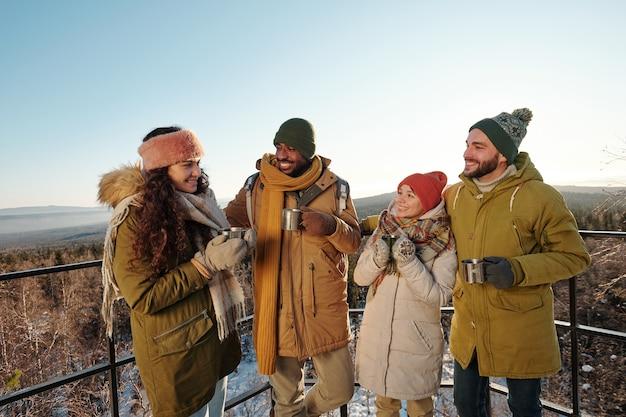 Szczęśliwi międzykulturowi przyjaciele w odzieży zimowej pijący gorącą herbatę podczas chłodu, stojąc na tle błękitnego nieba nad górami i lasem pokrytym śniegiem