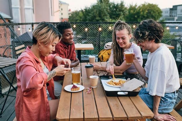 Szczęśliwi międzykulturowi przyjaciele z fast foodami i napojami w kawiarni na świeżym powietrzu