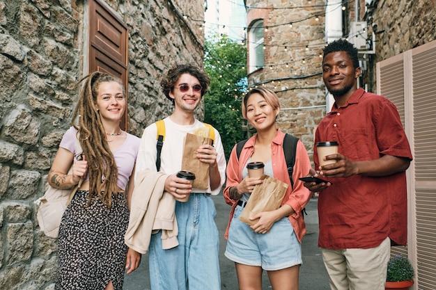 Szczęśliwi międzykulturowi przyjaciele z napojami i przekąskami stojącymi między kamiennymi budynkami
