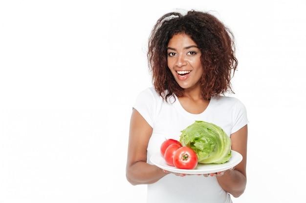 Szczęśliwi młodzi afrykańscy kobiety mienia warzywa.