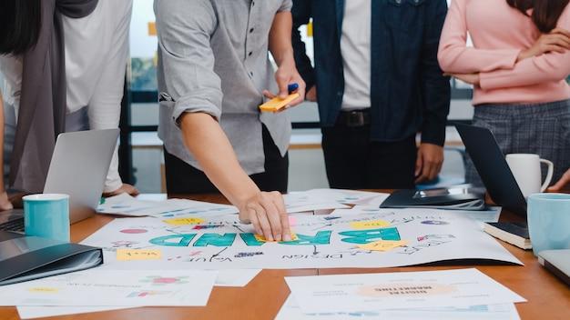 Szczęśliwi młodzi azjatyccy biznesmeni i kobiety biznesu spotykają się z pomysłami na burzę mózgów na temat nowego projektu papierkowej roboty