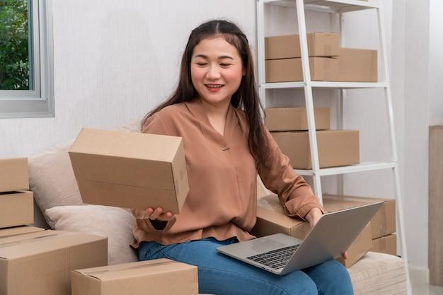Szczęśliwi młodzi azjatyccy przedsiębiorcy układają pudełka do dostarczania produktów klientom.