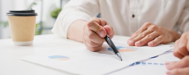 Szczęśliwi młodzi biznesmeni i kobiety biznesu z azji spotykają się podczas burzy mózgów na temat nowych współpracowników projektu papierkowego