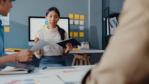 Szczęśliwi młodzi biznesmeni z azji i bizneswoman spotykają się podczas burzy mózgów nad nowymi pomysłami na projekt