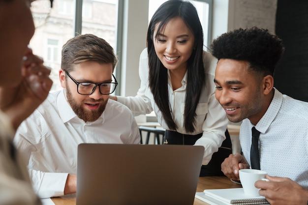 Szczęśliwi młodzi biznesowi koledzy używa laptop.