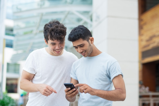 Szczęśliwi młodzi człowiecy używa smartphone podczas gdy badający nową aplikację