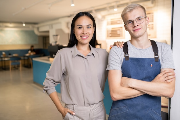 Szczęśliwi młodzi koledzy międzykulturowi w odzieży roboczej patrzą na ciebie, stojąc w nowoczesnej kawiarni lub restauracji