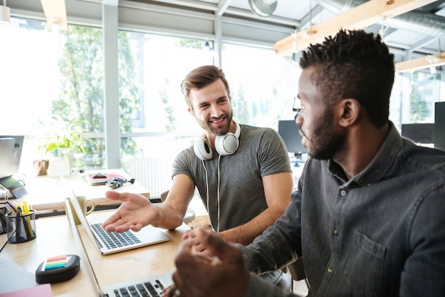 Szczęśliwi młodzi koledzy siedzi w biurowym coworking używać laptop