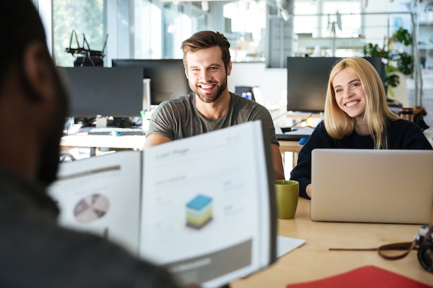 Szczęśliwi młodzi koledzy siedzi w biurowym coworking