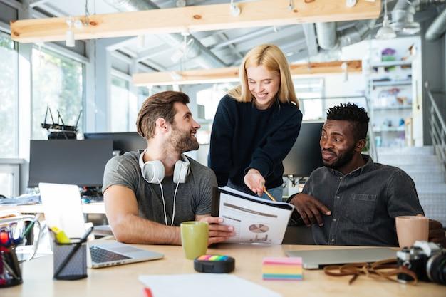 Szczęśliwi młodzi koledzy w biurowym coworking