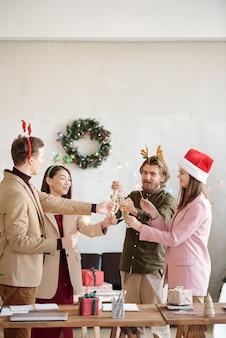 Szczęśliwi młodzi koledzy z bengalskimi światłami brzęczącymi kieliszkami szampana, wznoszący toast za sukces nad stołem z prezentami