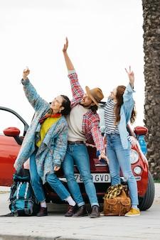 Szczęśliwi młodzi ludzie bierze selfie blisko czerwonego samochodu