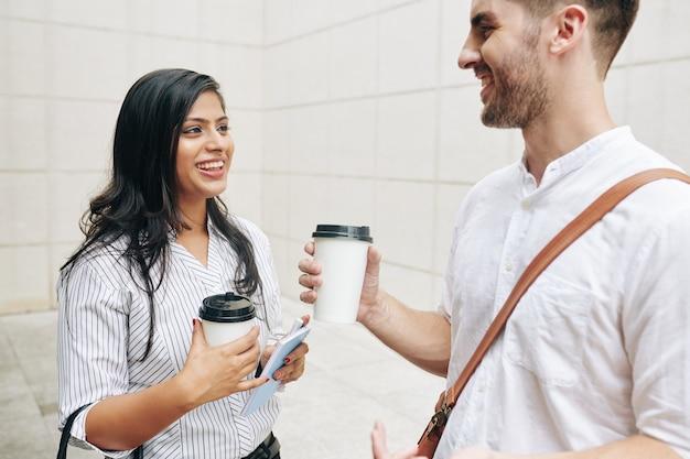 Szczęśliwi młodzi ludzie biznesu omawiają wiadomości i plotki podczas przerwy na kawę