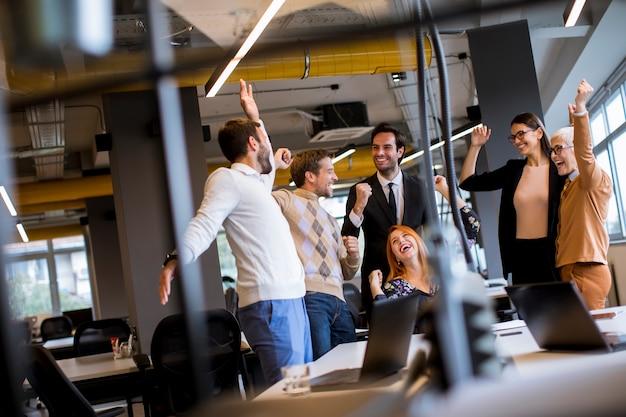 Szczęśliwi młodzi ludzie biznesu stoi w biurze i czeka na sukces w biurze