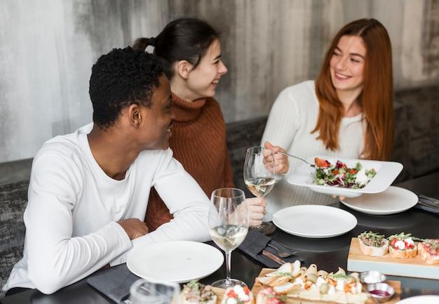 Szczęśliwi młodzi ludzie cieszy się kolację wpólnie