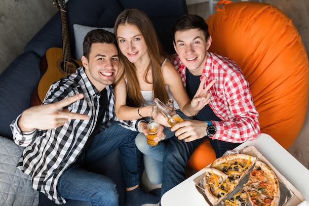 Szczęśliwi młodzi ludzie jedzą pizzę, piją piwo, opiekania, bawią się, impreza z przyjaciółmi w domu, towarzystwo hipsterów, dwóch mężczyzn, jedna kobieta, uśmiechnięta, pozytywna, pozuje do zdjęcia,