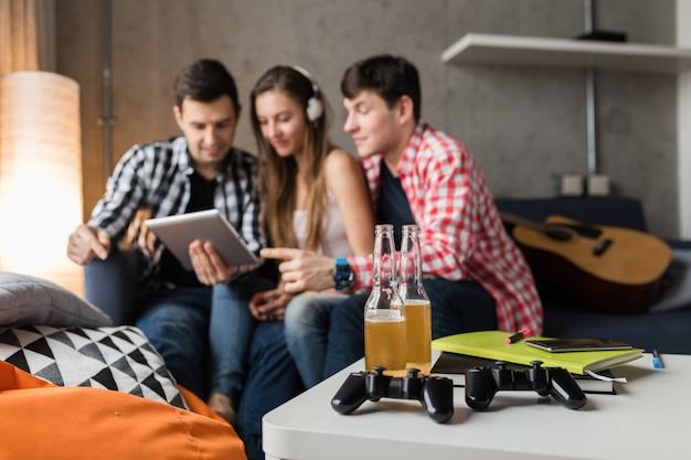 Szczęśliwi młodzi ludzie korzystający z tabletu, uczniowie uczący się, dobra zabawa, impreza z przyjaciółmi w domu, firma hipster razem, dwóch mężczyzn i jedna kobieta, uśmiechnięta, pozytywna, edukacja online, słuchanie muzyki