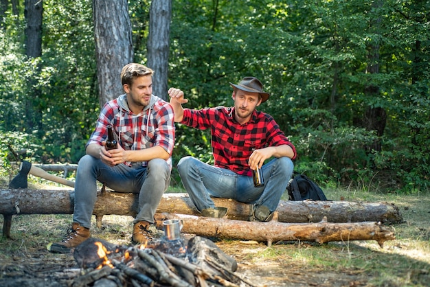 Szczęśliwi młodzi ludzie na kempingu w lesie letni styl życia młody chłopak na pikniku cieszący się kam...