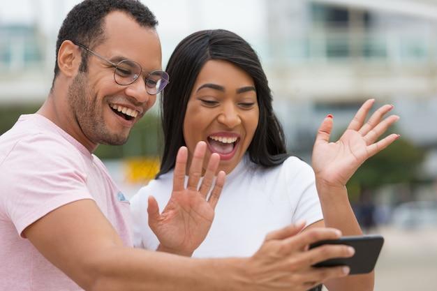 Szczęśliwi młodzi ludzie ono uśmiecha się kamera