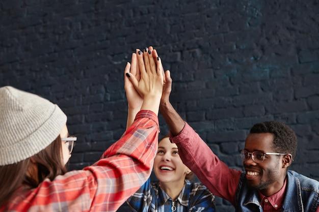Szczęśliwi młodzi ludzie przybijając piątkę, klepiąc się nawzajem w gratulacje podczas spotkania w kawiarni. kreatywni przedsiębiorcy w nieformalnych strojach śmieją się i świętują sukces projektu start-up