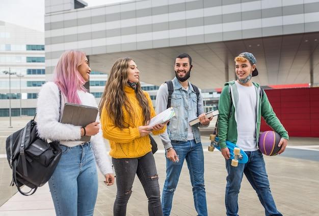 Szczęśliwi młodzi ludzie spotykający się na świeżym powietrzu i noszący maski na twarz podczas pandemii covid-19