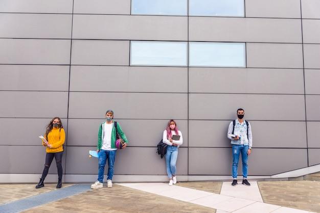 Szczęśliwi młodzi ludzie spotykający się na świeżym powietrzu i noszący maski na twarz podczas pandemii covid19