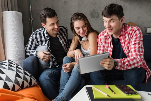 Szczęśliwi młodzi ludzie używający tabletu, uczniowie uczący się, dobrze się bawią, impreza z przyjaciółmi w domu, firma hipster razem, dwóch mężczyzn i jedna kobieta, uśmiechnięta, pozytywna, edukacja online