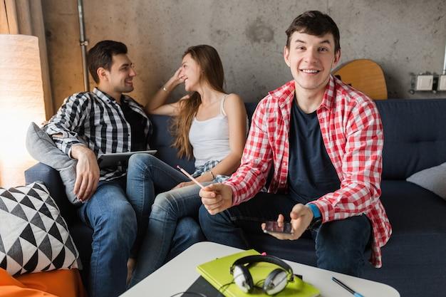 Szczęśliwi młodzi ludzie za pomocą tabletu, uczniowie uczą się, bawią się, impreza z przyjaciółmi w domu, firma hipster razem, dwóch mężczyzn i jedna kobieta, uśmiechnięta, pozytywna, edukacja online, mężczyzna trzyma telefon