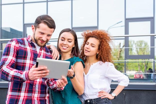 Szczęśliwi młodzi męscy i żeńscy przyjaciele patrzeje na cyfrowej pastylce stoi blisko szklanego budynku