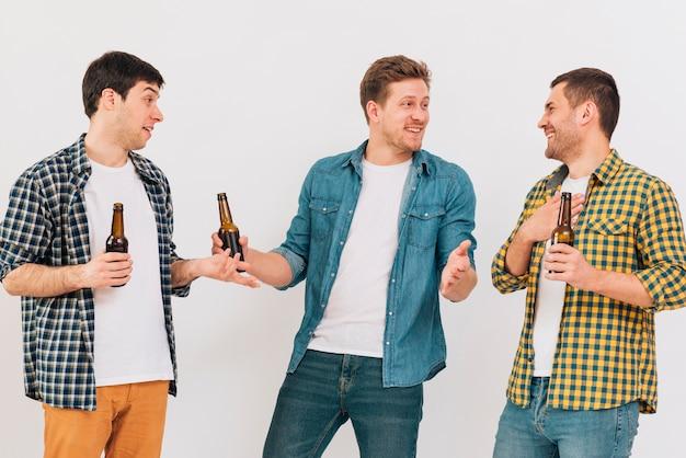 Szczęśliwi młodzi męscy przyjaciele trzyma piwną butelkę w ręce robi zabawie przeciw białemu tłu